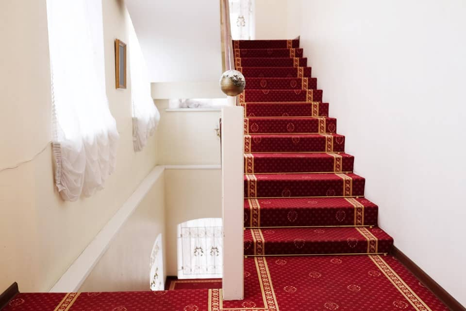 Stairs covered with red carpet in hotel